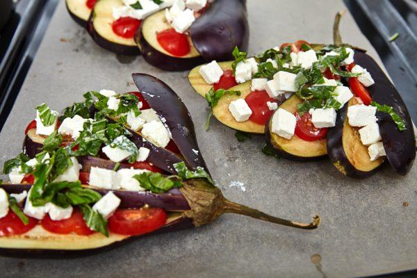 Присыпаем баклажаны фетой, чесноком и базиликом для веером запеченных баклажанов с помидорами и сыром фета