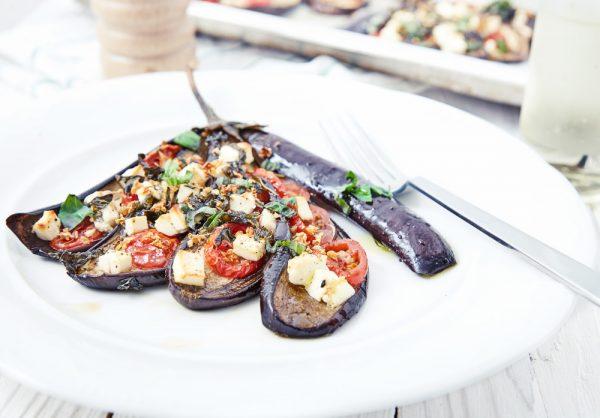 Выкладываем на тарелку, добавляем немного нарезанного базилика и подаем веером запеченные баклажанов с помидорами и сыром фета